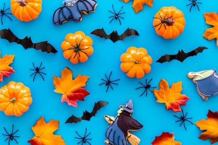 Nice halloween background with sweets. Cookies and pumpkins on blue top view. Imagens