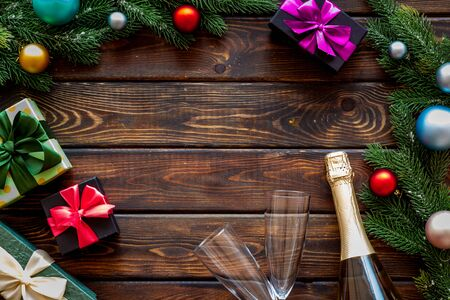 Boxes with presents, bottle and fir tree frame for christmas on wooden background top view mockup 版權商用圖片