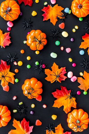 Bright Halloween composition with sweets and pumpkins on black background top view pattern