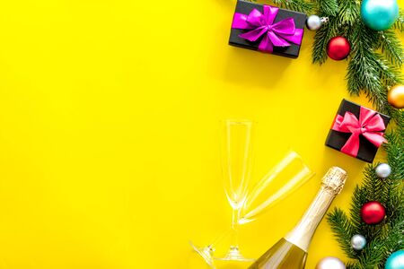 Celebration new year. Boxes with presents, champagne bottle and fir tree frame for christmas on yellow background top veiw mockup