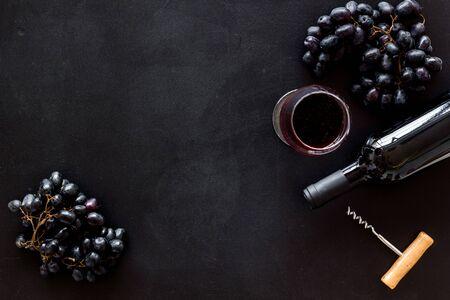 Red wine bottle near grape, wineglass and corkscrew Фото со стока - 129972597