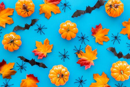 Halloween pattern with pumpkins, spiders and bats on blue background top view Imagens