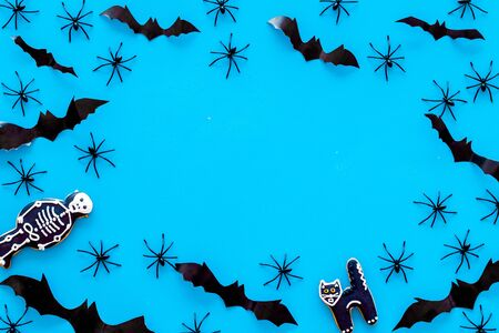 Cute Halloween decoration. Bats, spiders and special cookies on blue background top view. Stock Photo