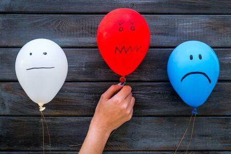 Concetto di emozioni negative. Palloncini con facce disegnate su sfondo di legno scuro vista dall'alto. Archivio Fotografico
