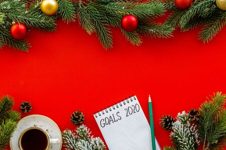 New Year goals concept. Notebook near New Year decoation like spruce branch and gifts.