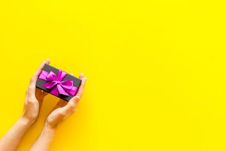 hands holding present in box on yellow background top view copyspace.