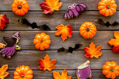 Bright Halloween composition with cookies and pumpkins on dark wooden background top view pattern Stok Fotoğraf