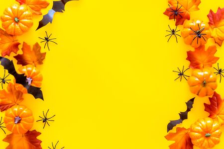 Halloween frame with pumpkins, spiders and bats on yellow background top view space for text