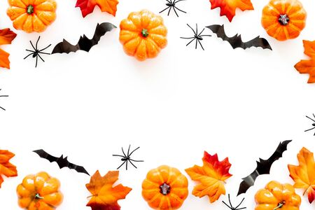 Halloween frame with pumpkins, spiders and bats on white background top view copy space