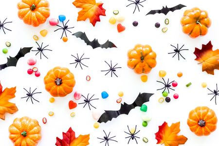 Bright halloween composition with sweets on white background top view pattern