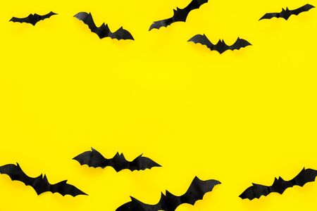 Bats cutout on Halloween frame on yellow table top view copy space Stock Photo