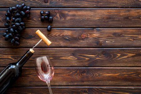 Open wine bottle. Top view dark wooden background copy space