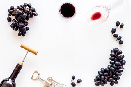 Testing wine concept. Wine bottle near black grape, wineglass and corkscrew