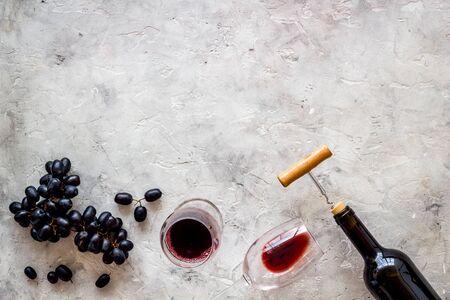 Red wine bottle near black grape, wineglass, corkscrew