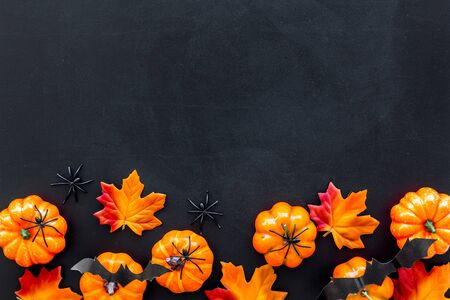 Nice halloween background. Small spiders among leaves and pumpkins on black top view. Stok Fotoğraf