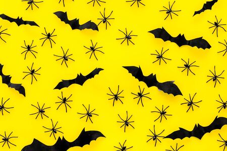 Stylish Halloween design. Bats and spiders on yellow background top view pattern Stock Photo