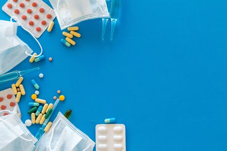 Treat flu and cold concept. Vaccine, mask, pills on blue background top view frame space for text