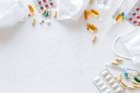Treat flu and cold concept. Vaccine, mask, pills on white background top view frame copy space