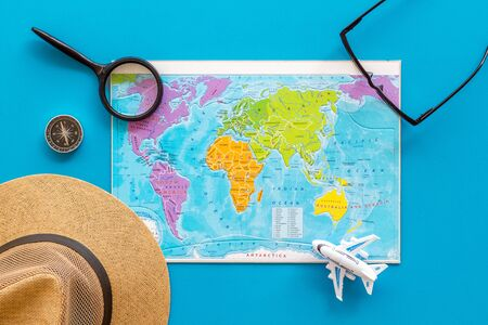 Planning a travel concept. Map of the world and tourist accessories on blue background top view