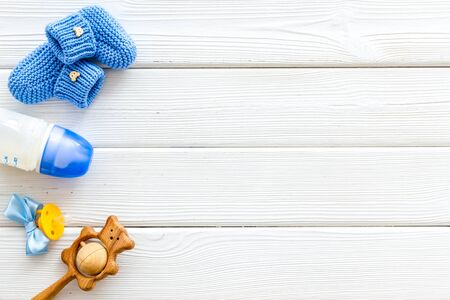 Blue knitted footwear and rattle, bottle, dummy for baby on white wooden background top view mockup