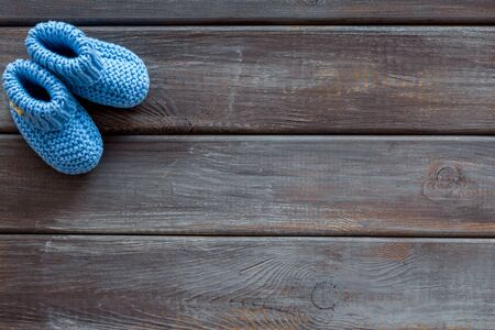 Blue knitted footwear for kids on wooden background top view space for text Stock Photo