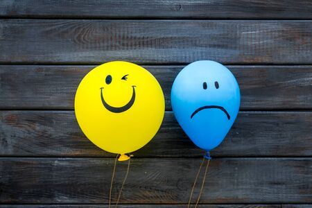 Treat depression concept. Balloons with sad and smiling faces on dark wooden background top view
