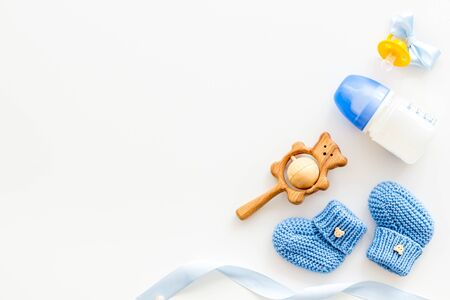 Blue knitted footwear and rattle, bottle, dummy for baby on white background top view mockup Stock Photo