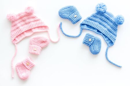 Knitted blue and pink footwear and hat for baby on white background top view mockup