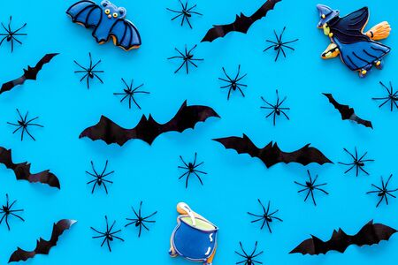 Cute Halloween decoration. Bats, spiders and special cookies on blue background top view pattern