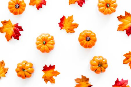 Autumn composition. Pattern with red and orange leaves and pumpkins on white background top view Stok Fotoğraf