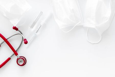 Medical background with face mask, stethoscope, vaccine on white background top view copy space