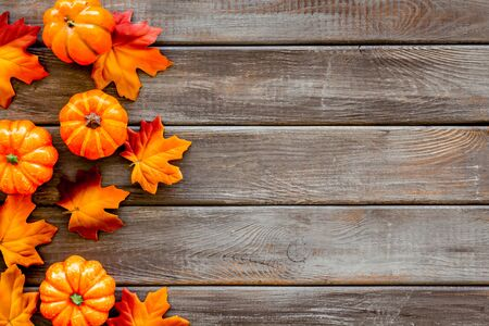 Autumn background with leaves and pumpkins on dark wooden top view space for text frame Stok Fotoğraf