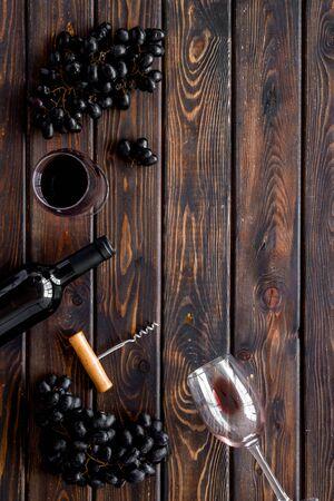 Red wine bottle near wineglass on dark wooden background top view copy space Фото со стока - 130268171