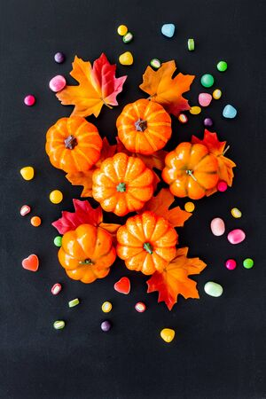 Bright Halloween composition with sweets and pumpkins on black background top view 写真素材
