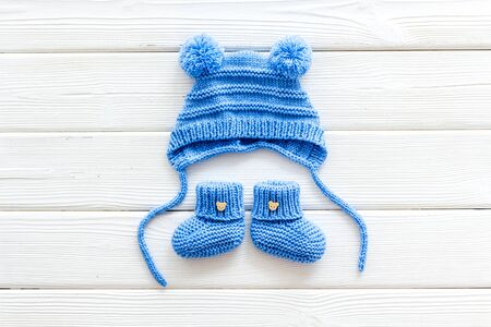 Blue knitted set for kids on white wooden background top view