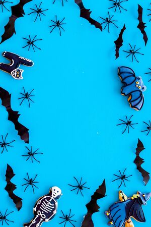 Cute Halloween decoration. Bats, spiders and special cookies on blue background top view copy space