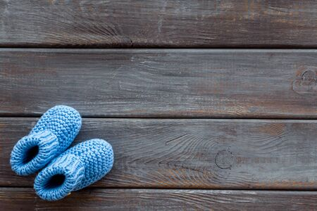 Knitted blue footwear for baby on wooden background top view mockup