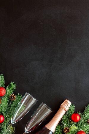 Nieuwjaarsdecoratie met champagnefles en dennentakken op zwarte achtergrond bovenaanzicht frame kopie ruimte