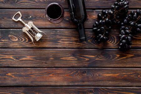 Red wine bottle near wineglass on dark wooden background top view copy space Фото со стока - 130363563