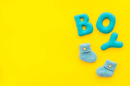 Childrens birthday concept. Word boy near booties on yellow background top view frame copy space