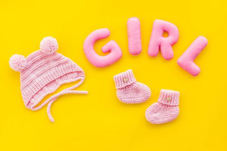 Decoration for babys birthday. Word girl near booties on yellow background top view