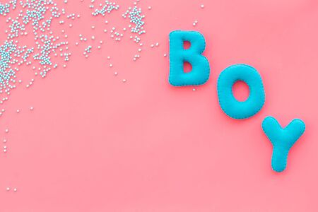 Boy word as decoration for baby shower on pink background top view frame copy space