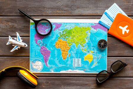 Planning a travel concept. Map of the world and tourist accessories on dark wooden background top view