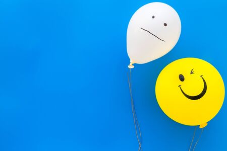 Treat depression concept. Balloons with frustrated and smiling faces on blue background top view space for text