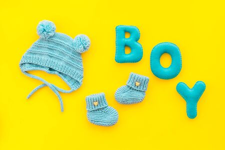 Childrens birthday concept. Word boy near booties on yellow background top view. Stockfoto