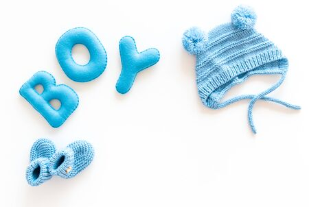 Childrens birthday concept. Word boy near booties on white background top view.