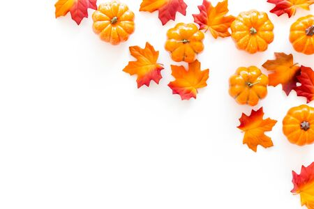 Autumn background with red and orange leaves and pumpkins on white top view