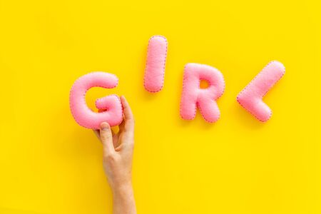 Girl word as decoration for baby shower on yellow background top view.