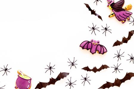 Cute Halloween decoration. Bats, spiders and special cookies on white background top view.