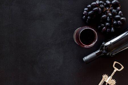 Red wine bottle near grape, wineglass and corkscrew Фото со стока - 130430502